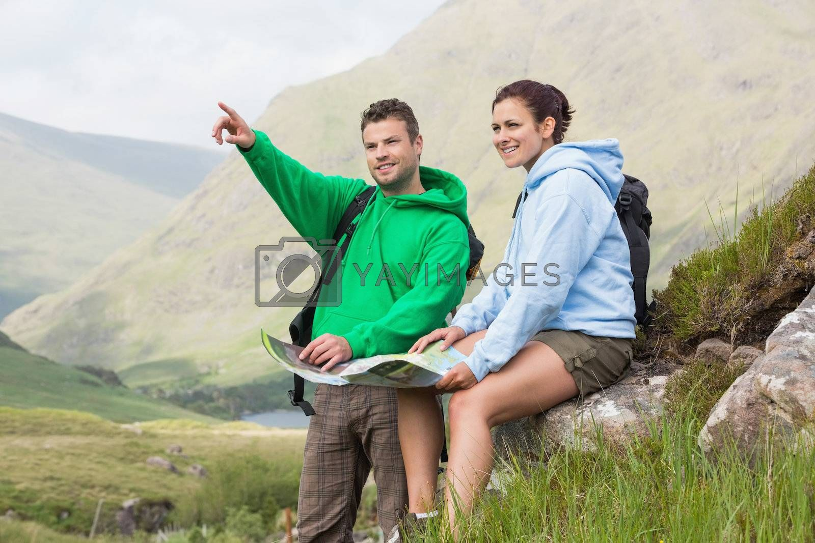 Couple resting after hiking uphill and consulting map by Wavebreakmedia