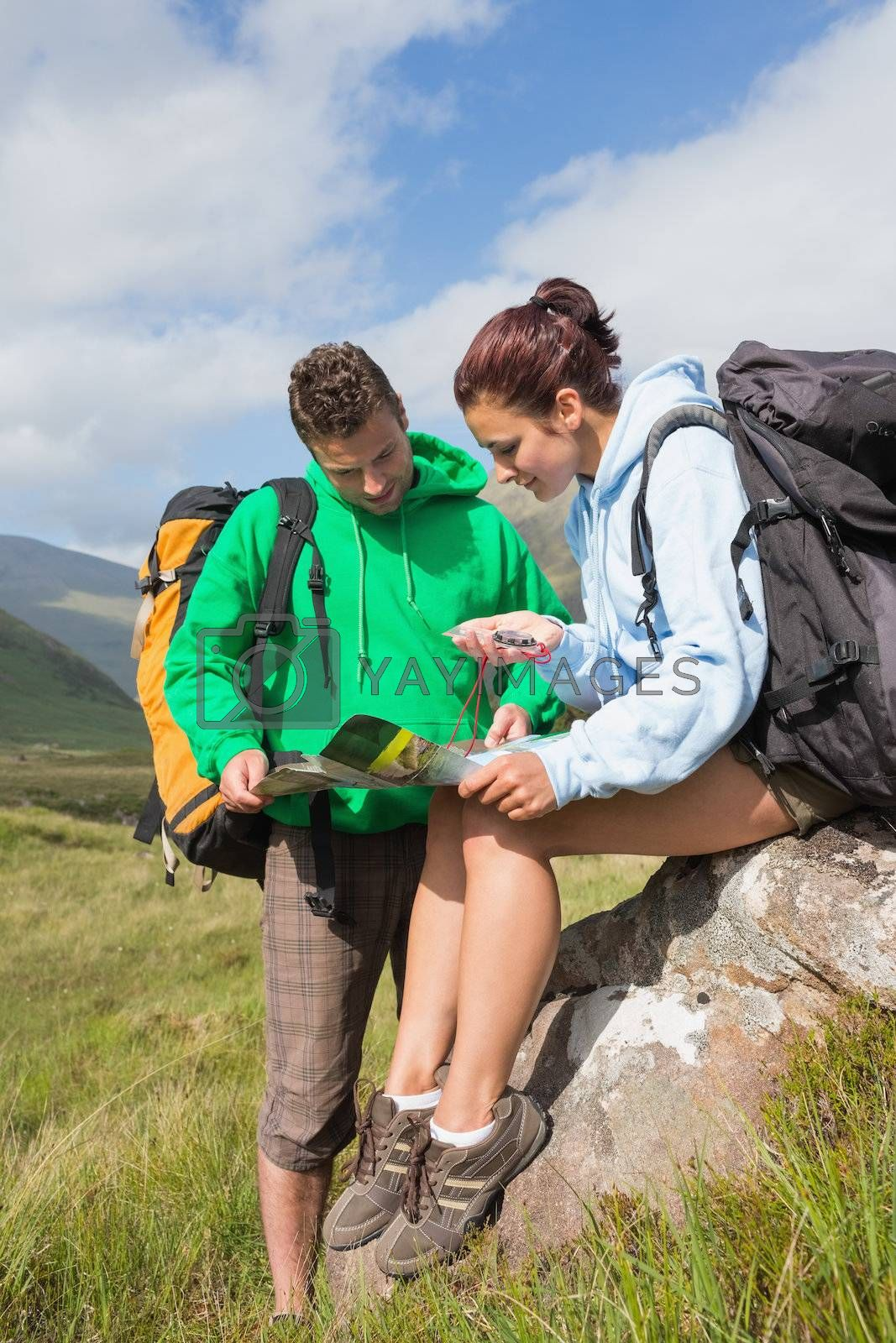 Attractive couple resting after hiking uphill and consulting map by Wavebreakmedia