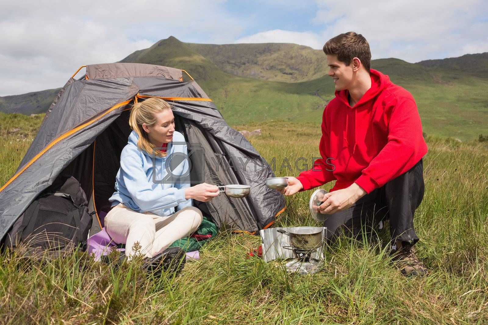 Cheerful couple cooking outdoors on camping trip by Wavebreakmedia