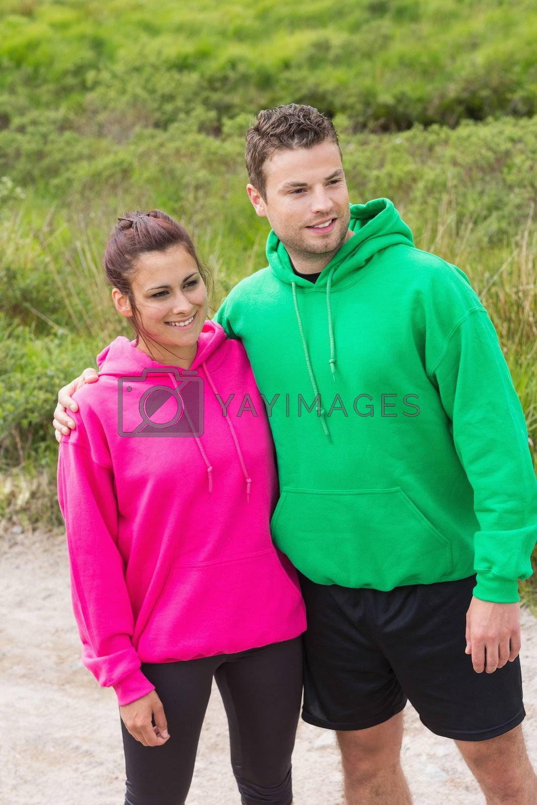 Athletic couple looking ahead and embracing by Wavebreakmedia