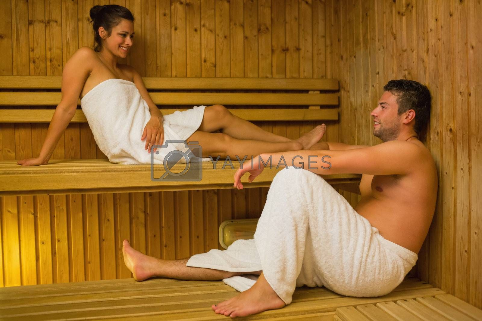 Happy couple relaxing in a sauna and chatting by Wavebreakmedia
