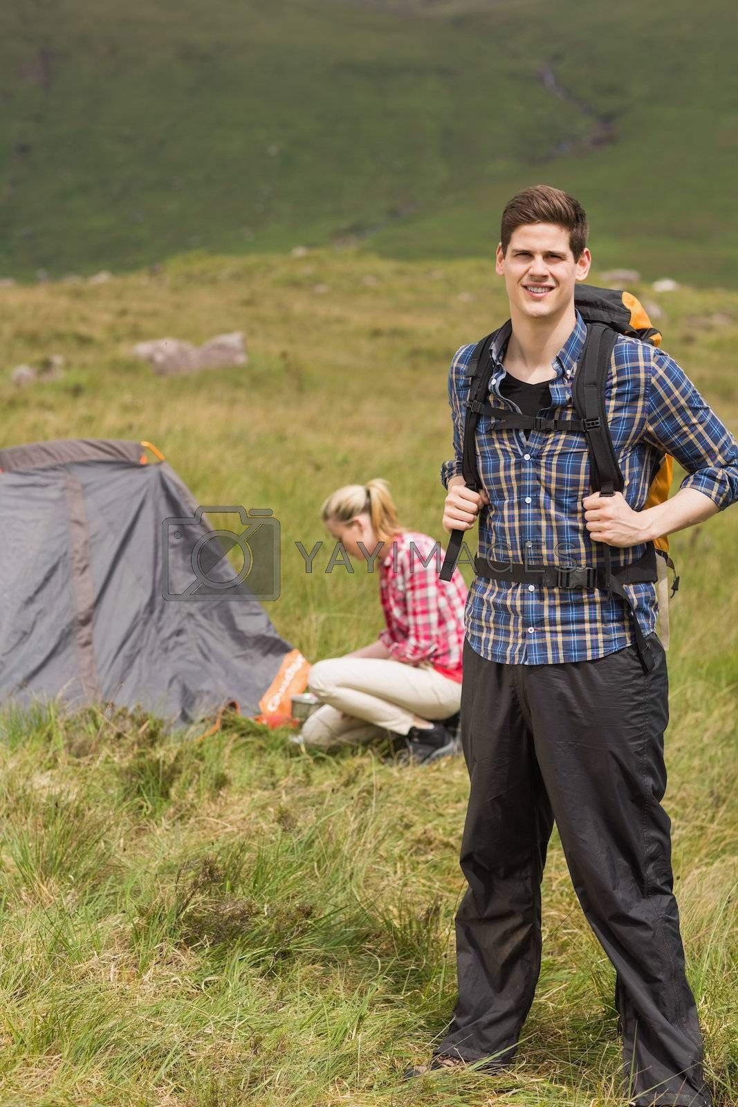 Happy man carrying backpack while girlfriend is pitching tent by Wavebreakmedia