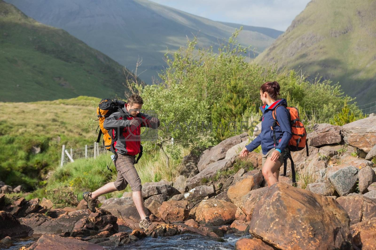 Couple crossing a river on a hike by Wavebreakmedia