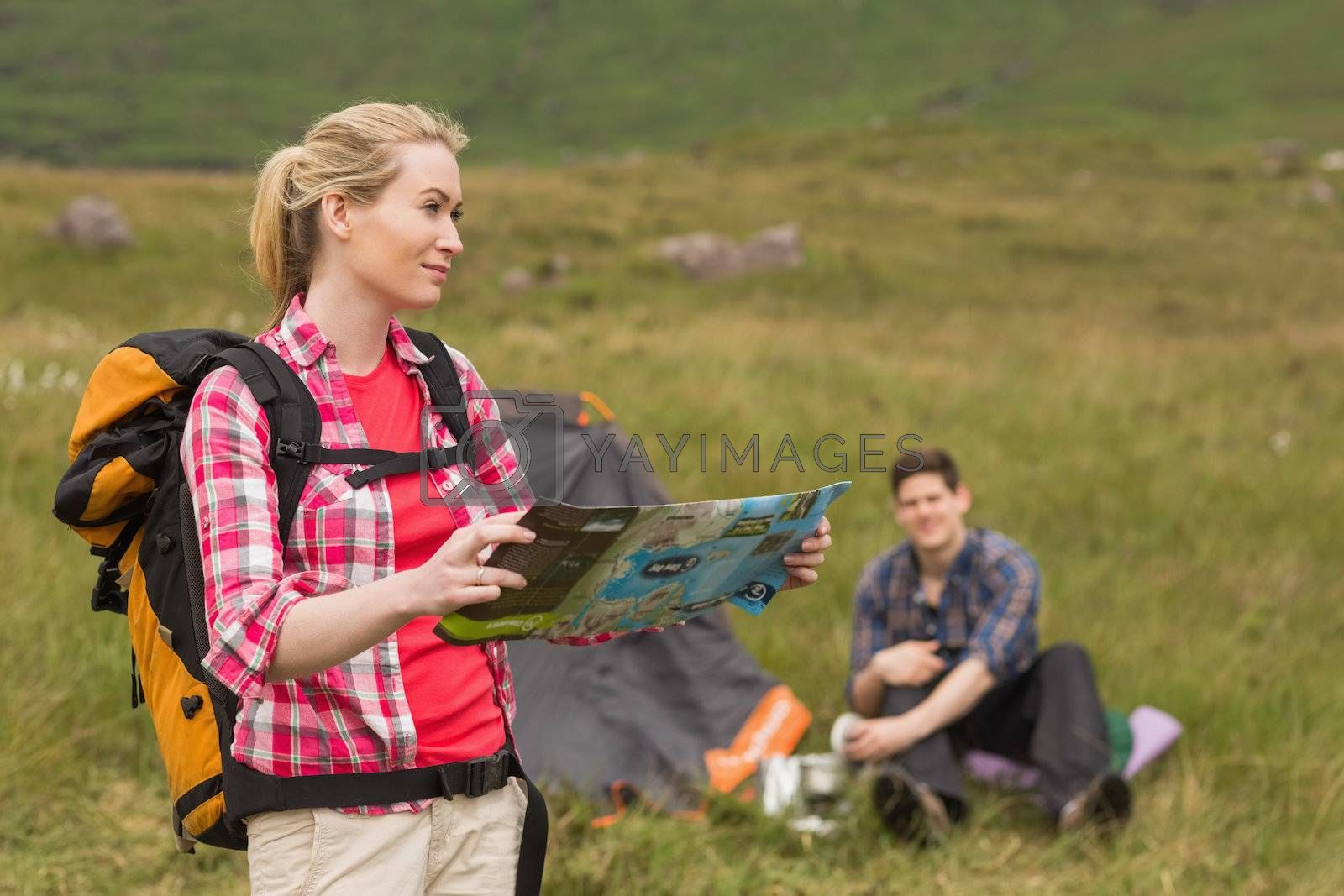 Smiling woman carrying backpack and holding map by Wavebreakmedia
