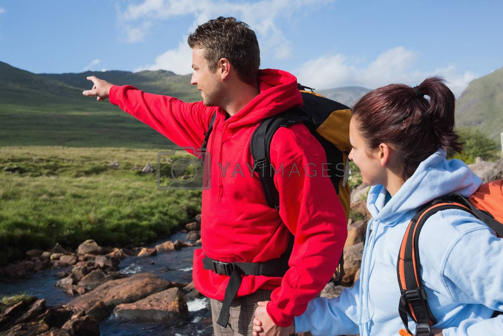 Couple standing at edge of river on hike with man pointing by Wavebreakmedia