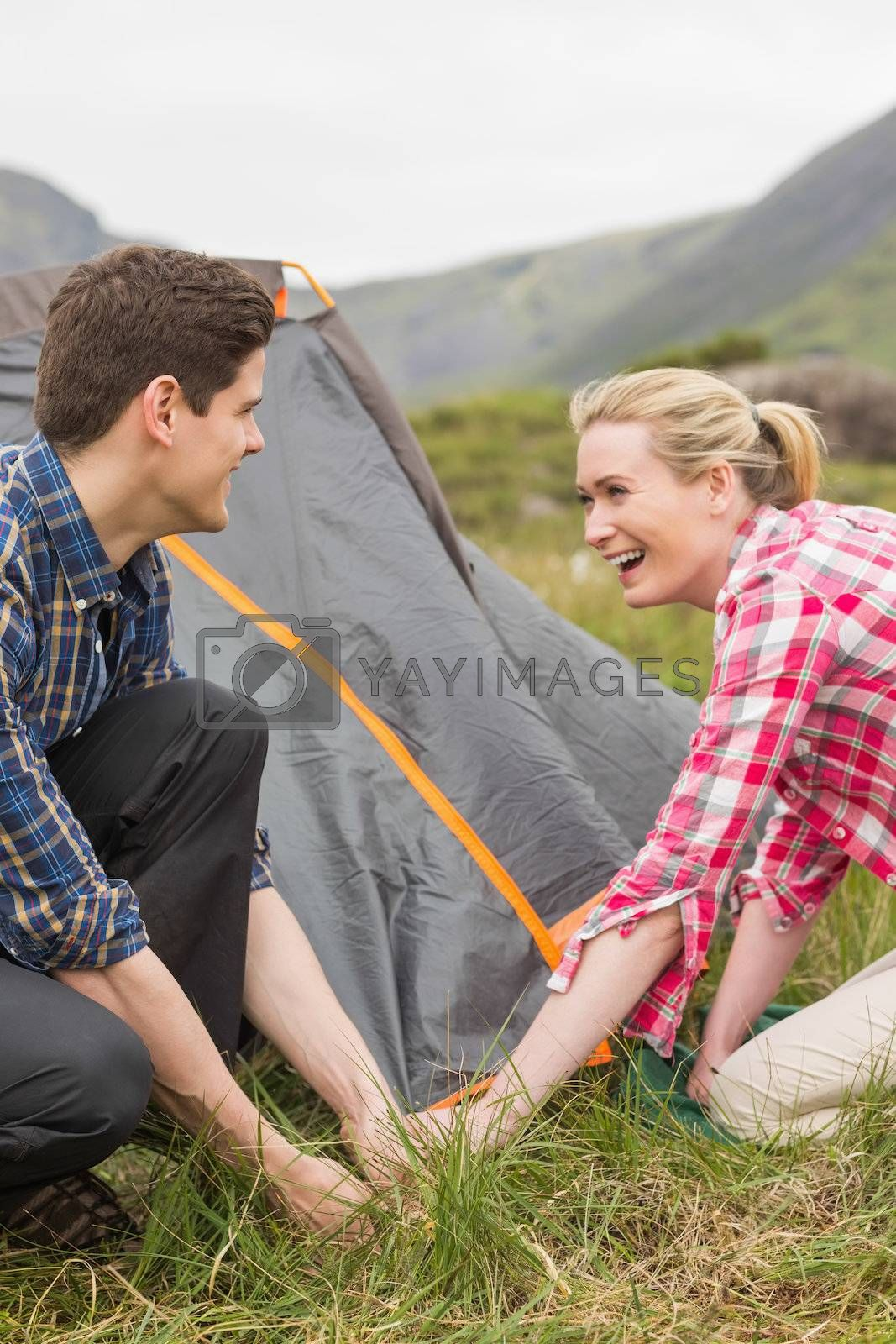 Smiling couple pitching their tent together by Wavebreakmedia