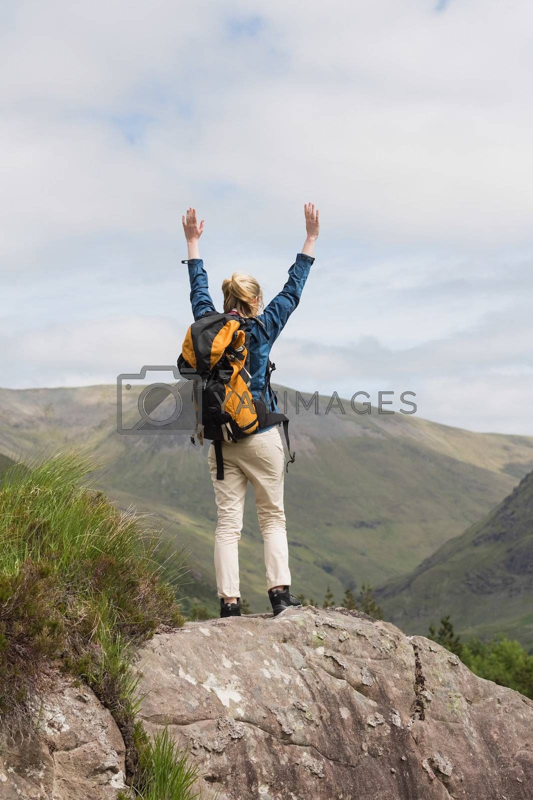Woman standing on rock cheering after a hike by Wavebreakmedia