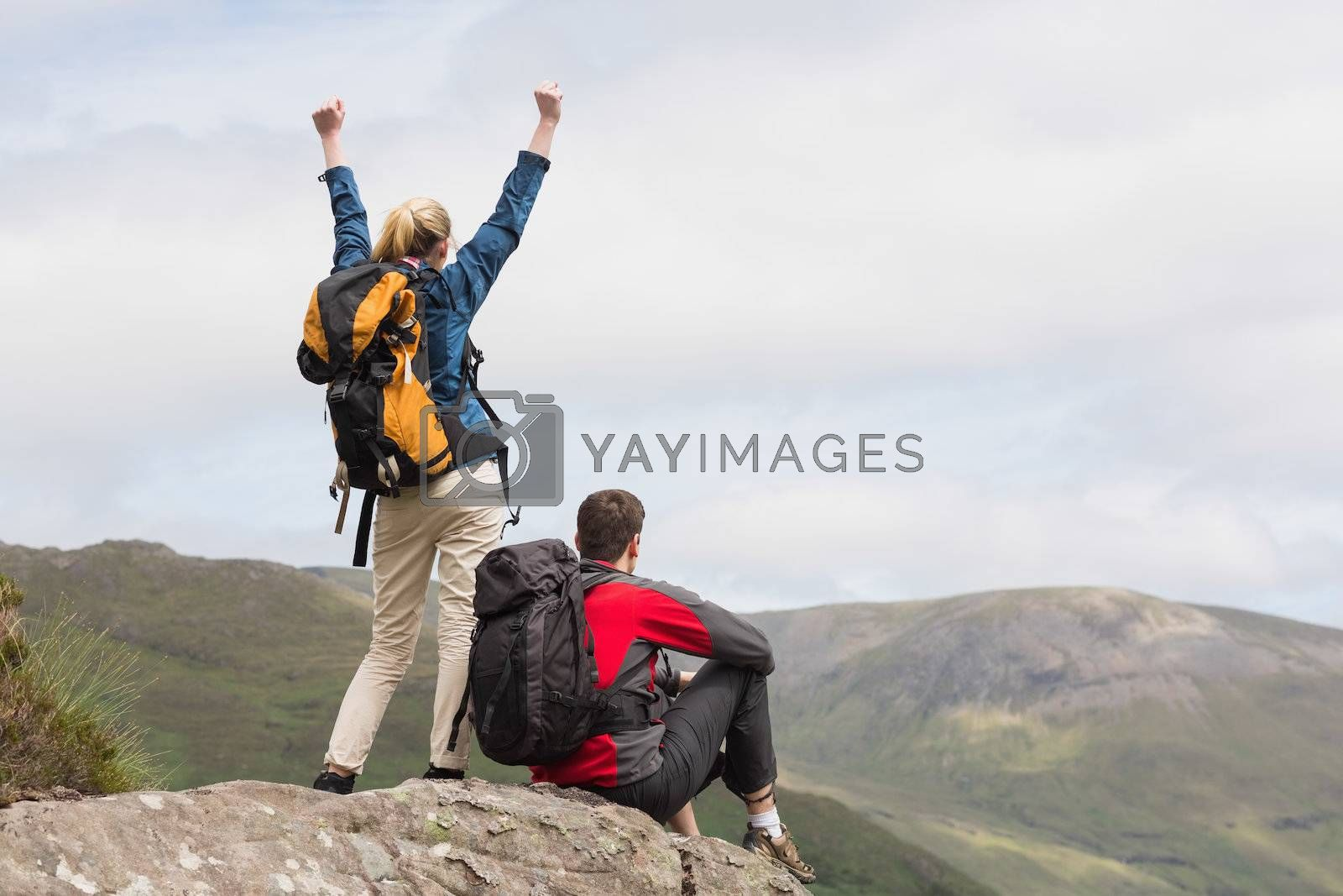 Excited couple reaching the top of their hike by Wavebreakmedia