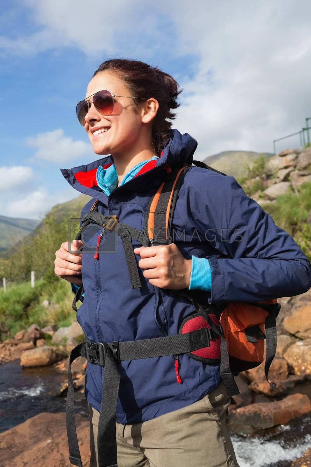 Brunette wearing rain jacket and sunglasses smiling by Wavebreakmedia
