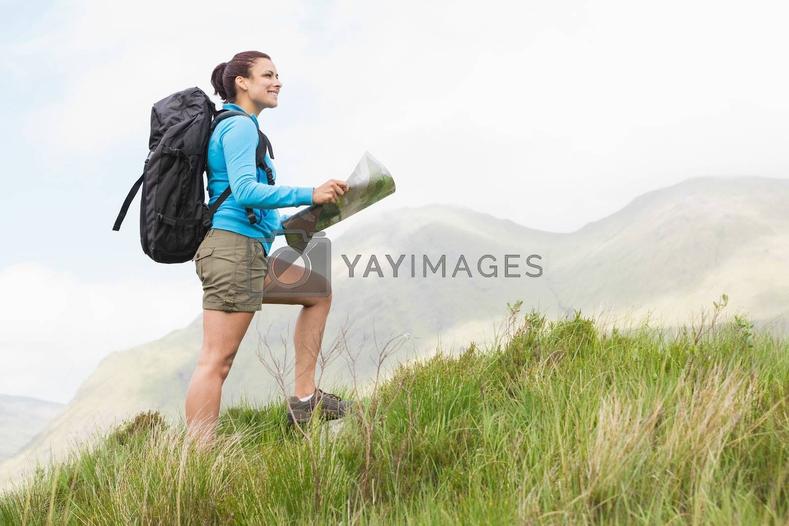 Attractive hiker with backpack hiking uphill holding a map by Wavebreakmedia