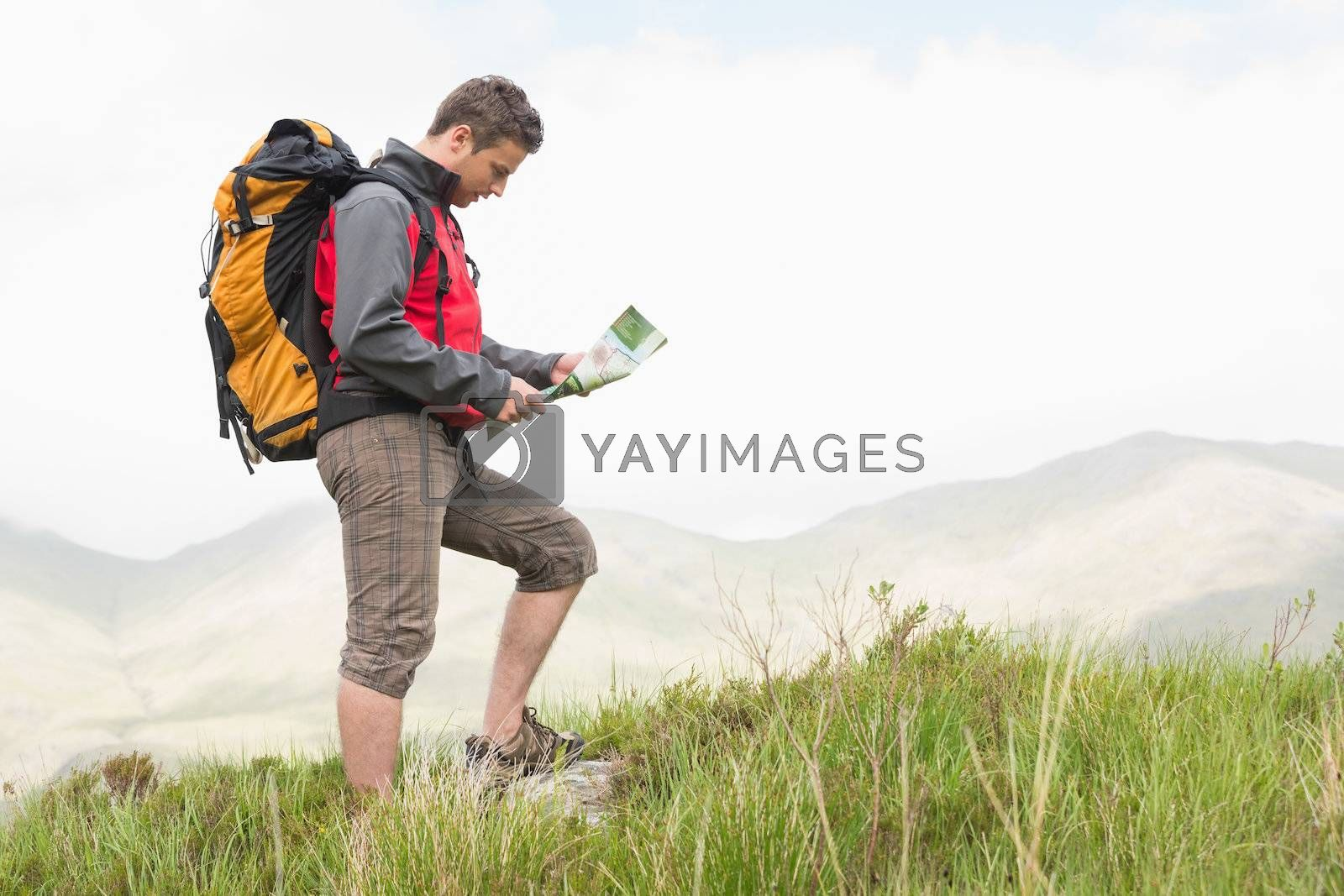 Handsome hiker with backpack hiking uphill reading a map by Wavebreakmedia