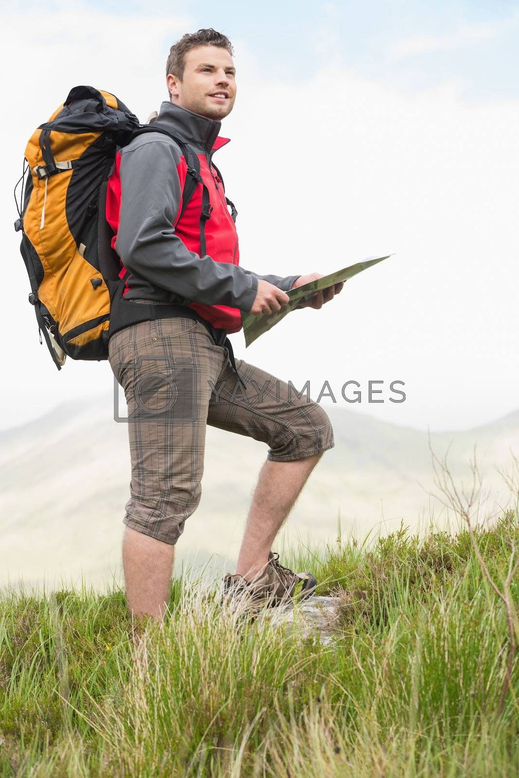 Handsome hiker with rucksack walking uphill holding a map by Wavebreakmedia