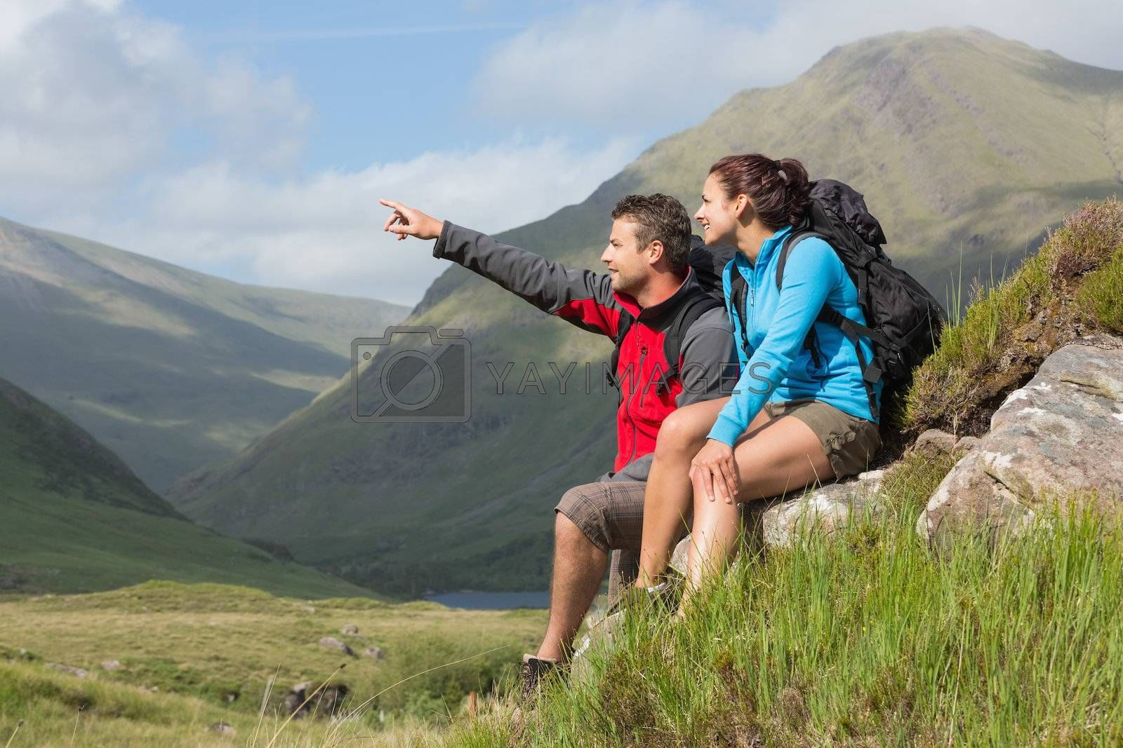 Couple taking a break after hiking uphill with man pointing by Wavebreakmedia