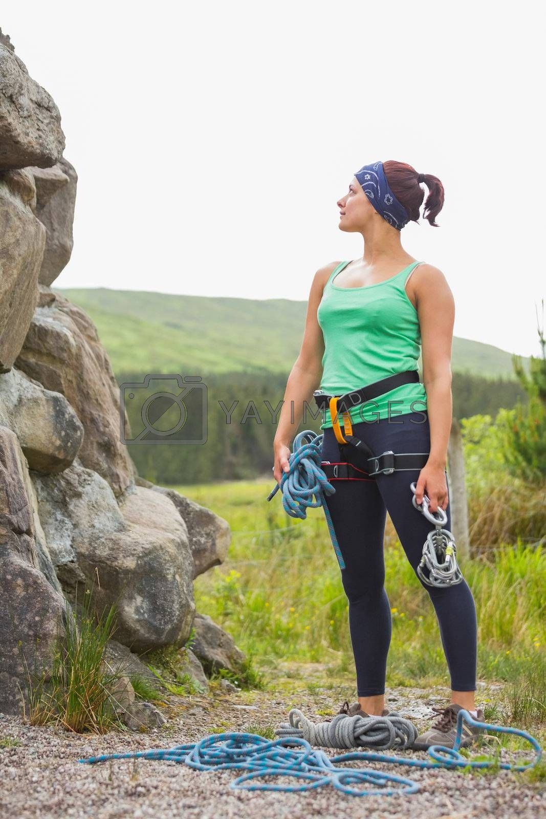 Attractive rock climber looking up at her challenge by Wavebreakmedia