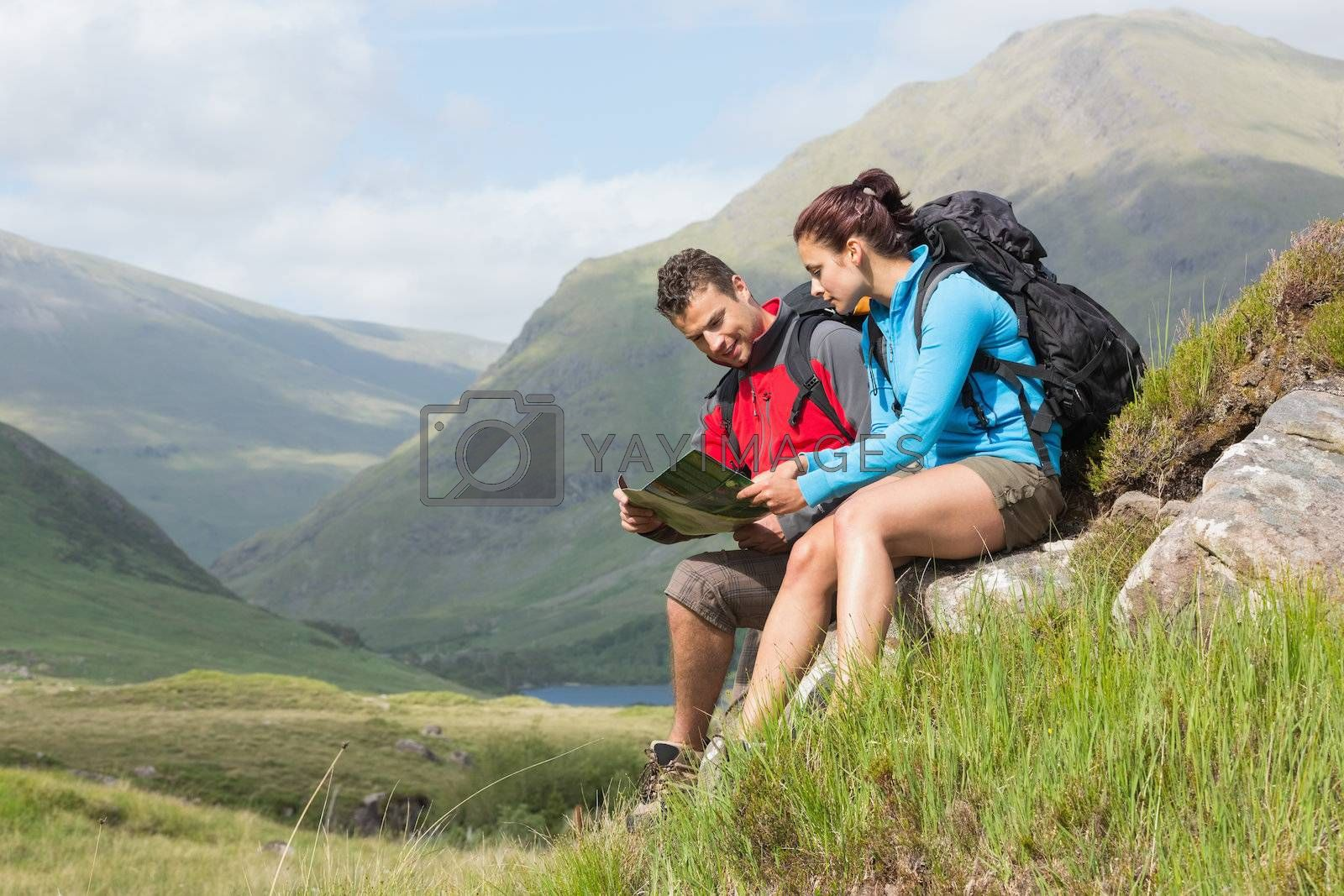 Couple taking a break after hiking uphill and reading map by Wavebreakmedia
