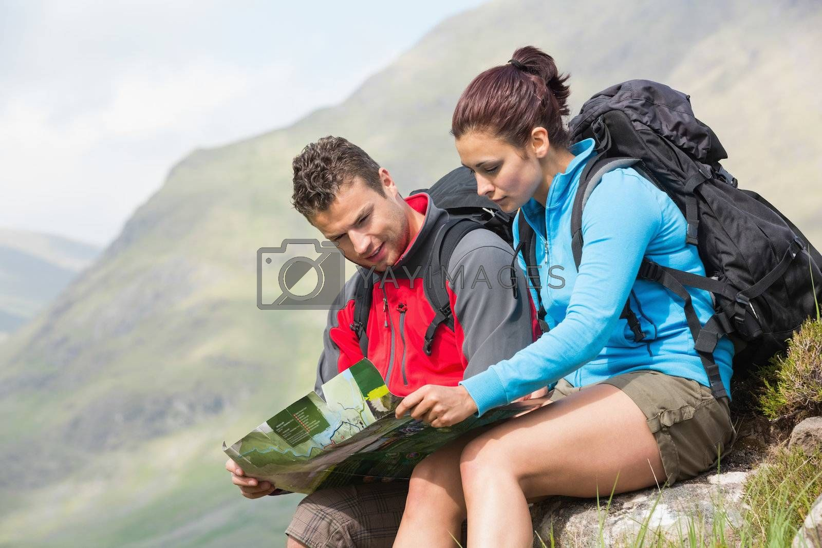 Couple resting after hiking uphill and reading map by Wavebreakmedia