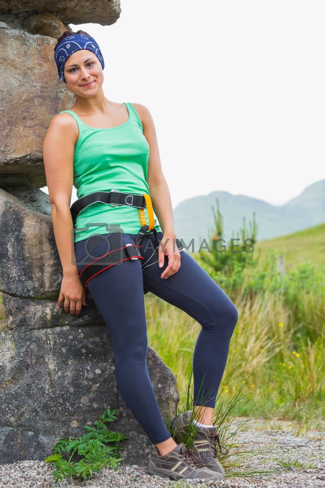 Attractive female rock climber leaning on rock face smiling  by Wavebreakmedia