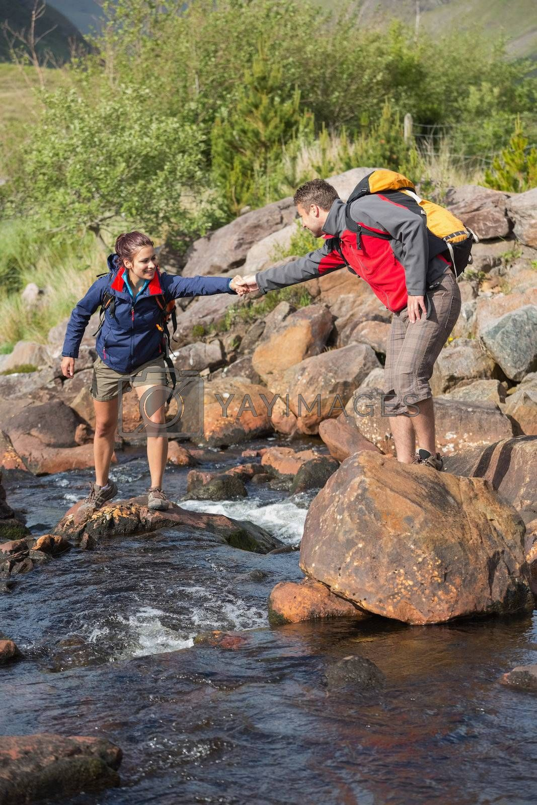 Man helping his girlfriend to cross a river by Wavebreakmedia