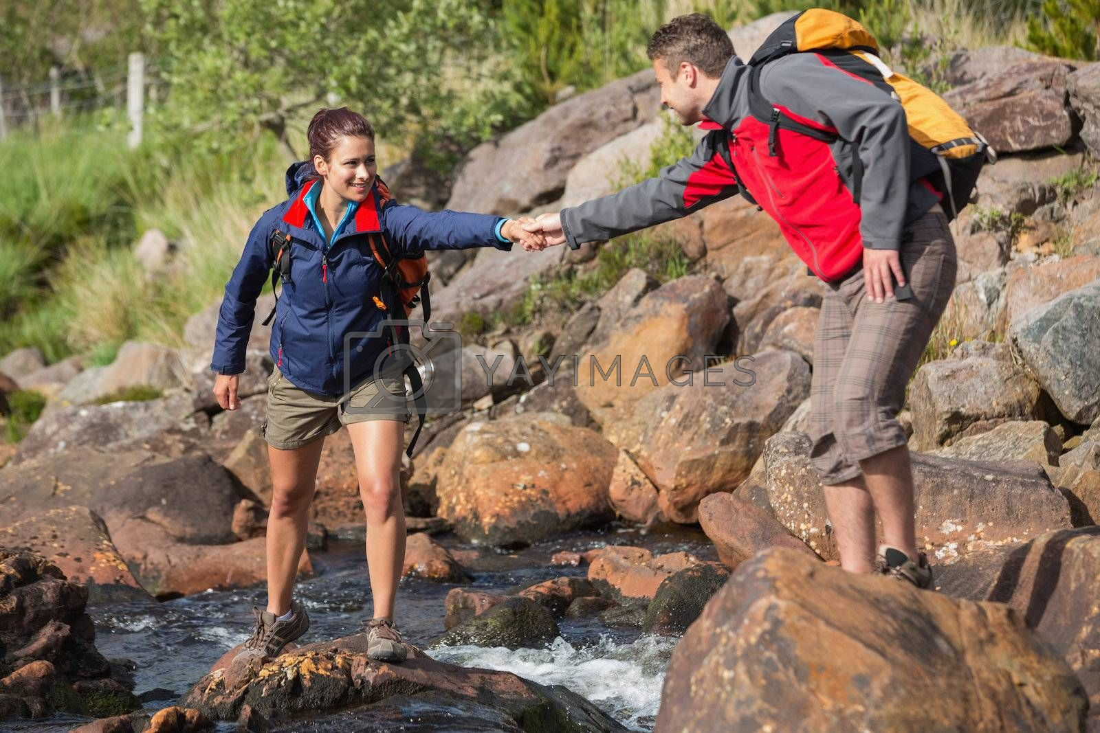 Man helping his smiling girlfriend to cross a river by Wavebreakmedia