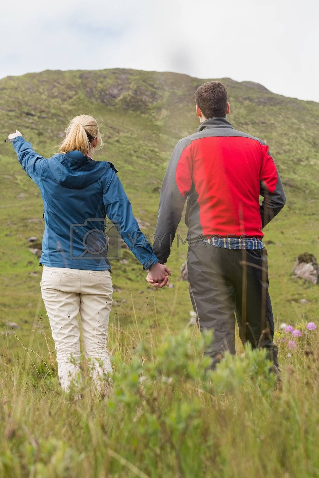 Couple holding hands with woman pointing to mountain by Wavebreakmedia