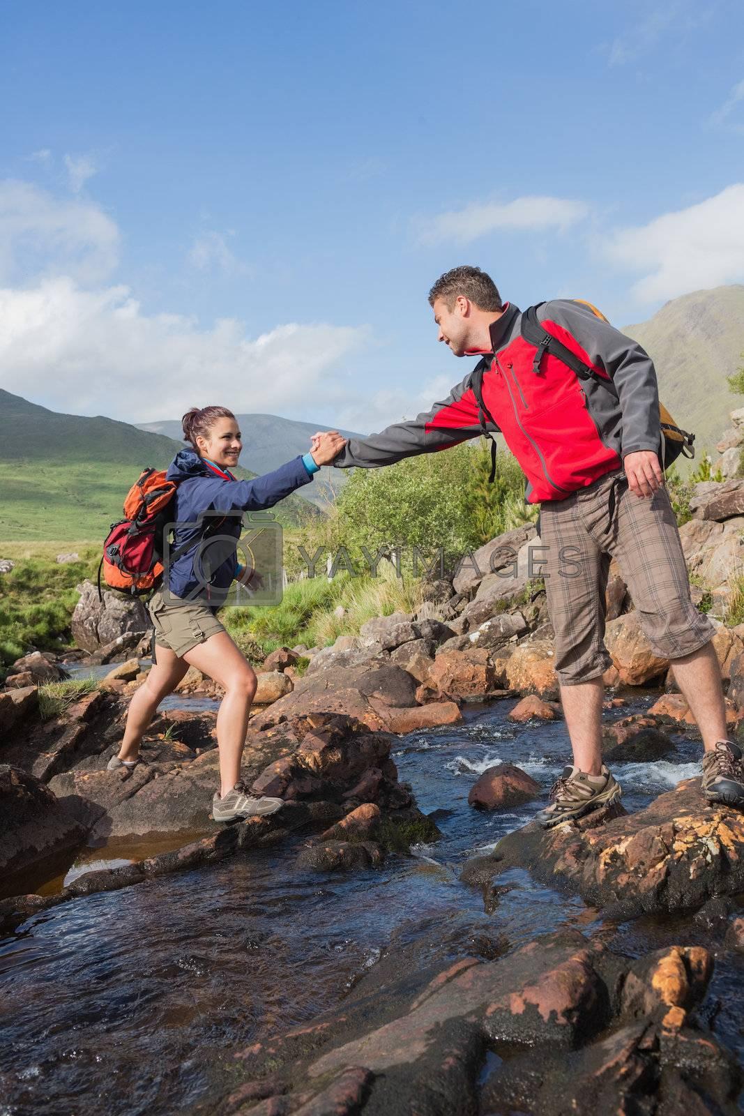 Man helping his pretty girlfriend to cross a river by Wavebreakmedia
