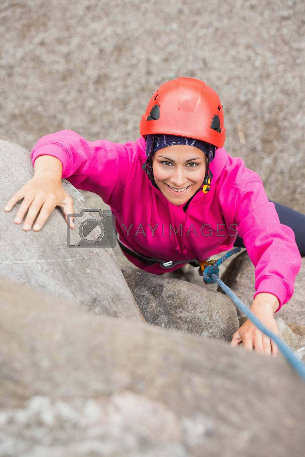 Happy girl climbing up rock face  by Wavebreakmedia
