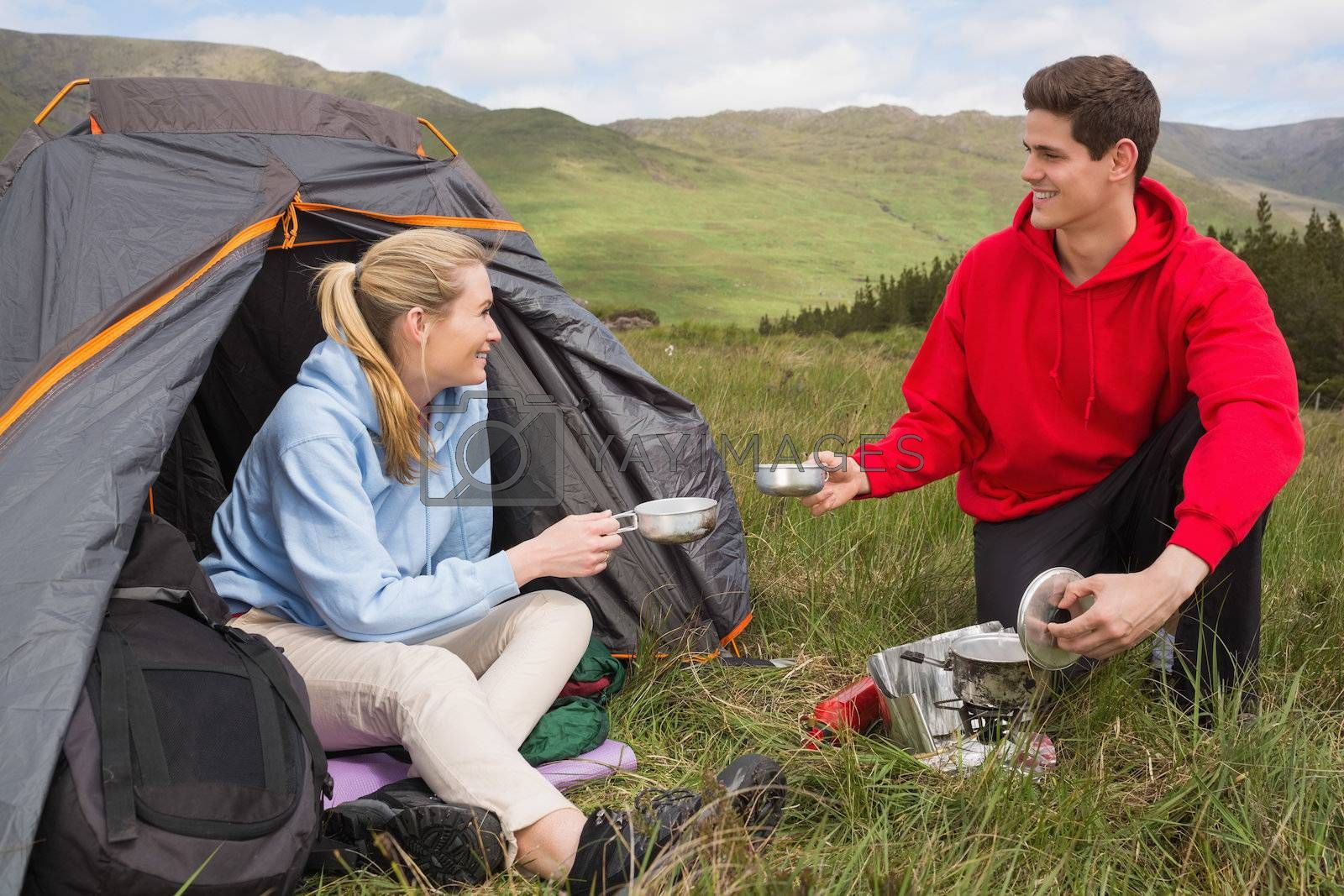 Happy couple cooking outdoors on camping trip by Wavebreakmedia