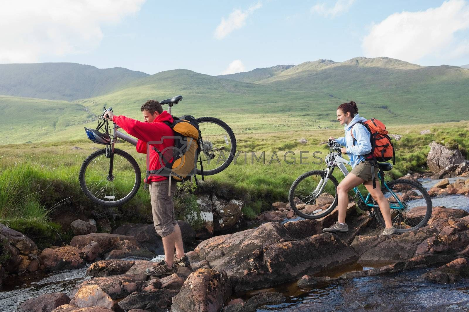 Couple crossing a stream holding their bikes by Wavebreakmedia