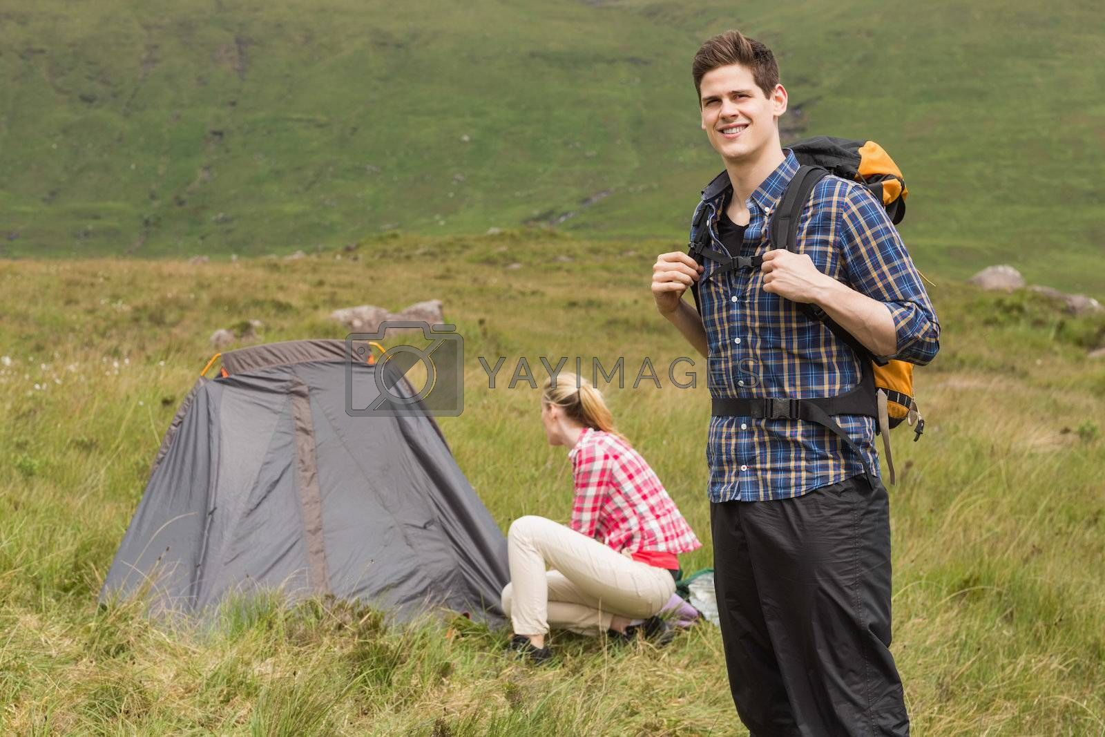 Smiling man carrying backpack while girlfriend is pitching tent by Wavebreakmedia