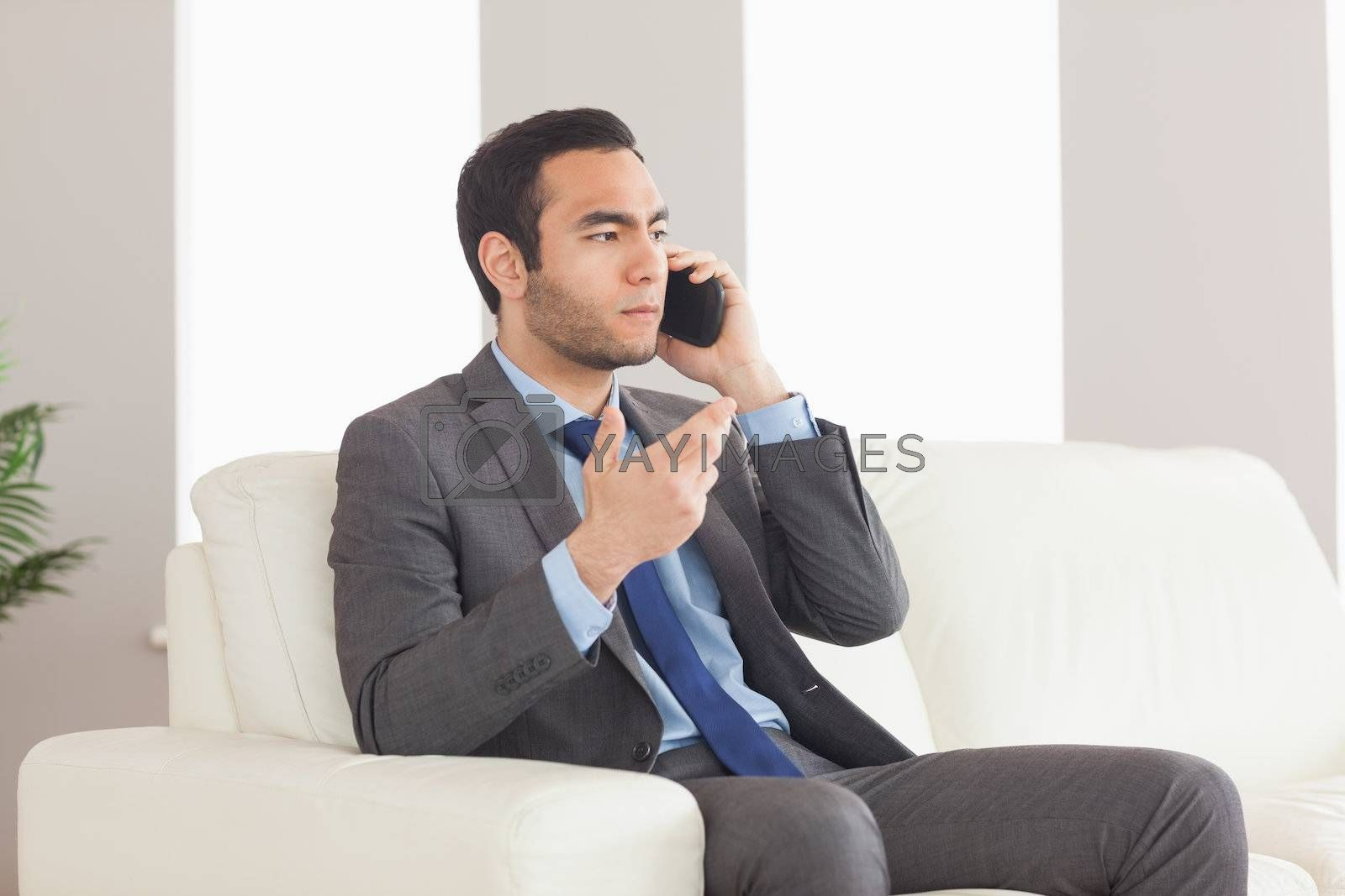 Serious businessman on the phone sitting on cosy sofa by Wavebreakmedia