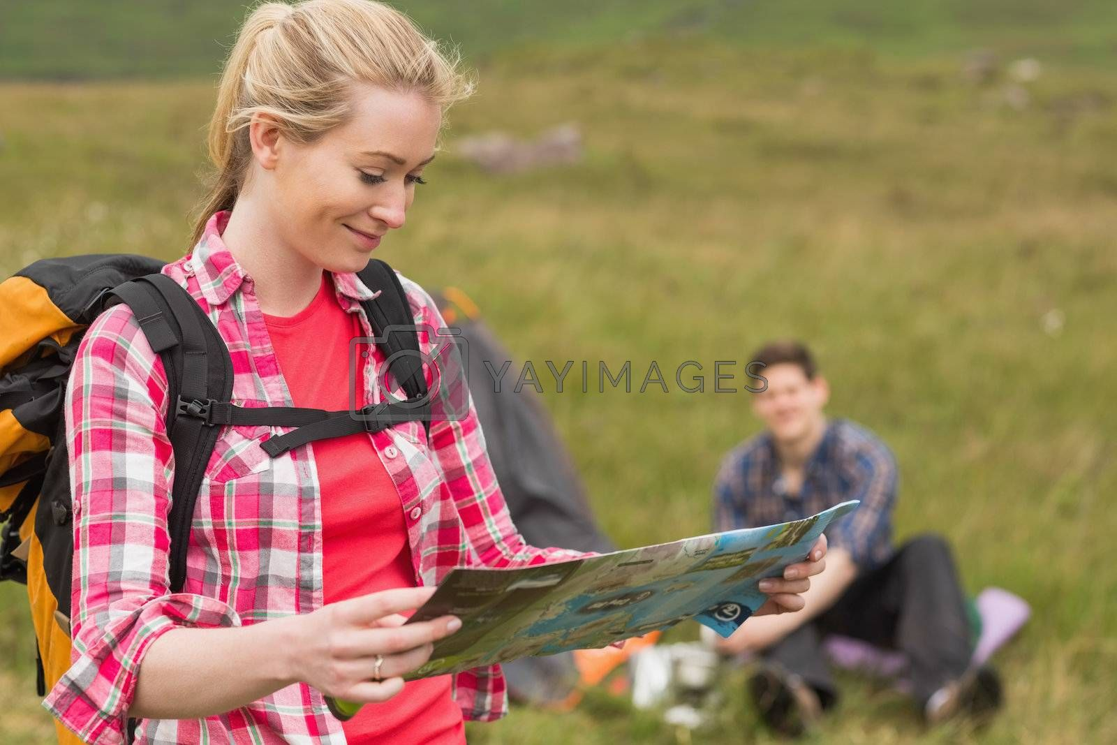 Happy woman carrying backpack and holding map by Wavebreakmedia