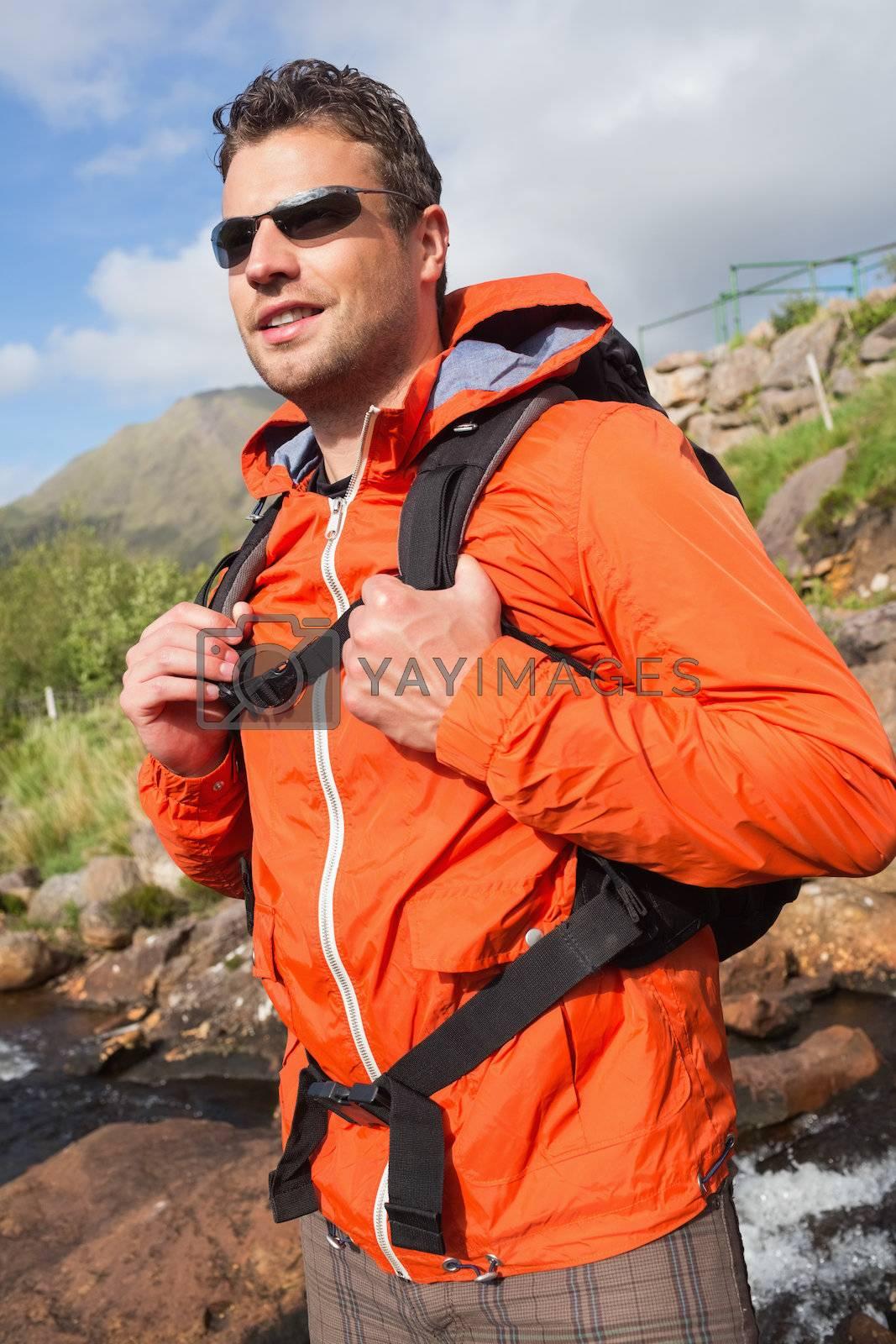 Man wearing rain jacket and sunglasses smiling by Wavebreakmedia