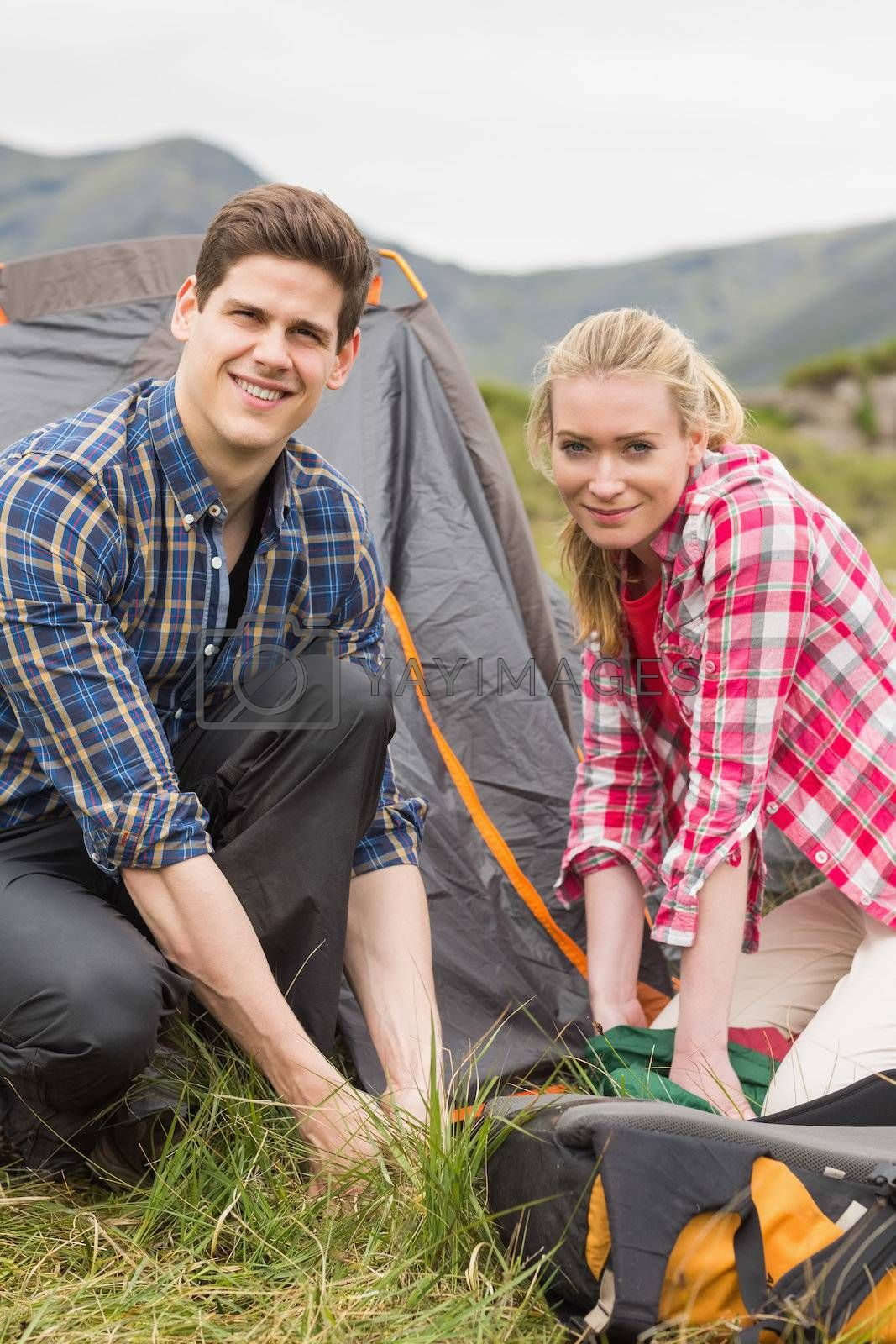 Happy couple pitching their tent together by Wavebreakmedia