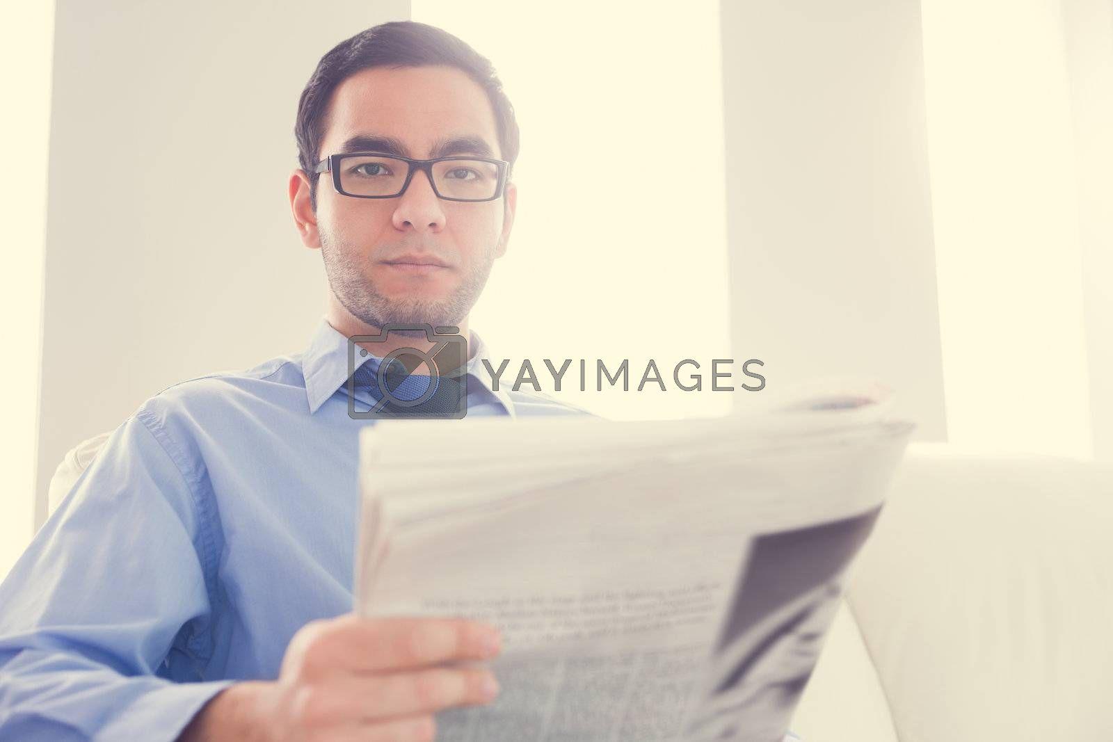 Frowning man looking at camera and holding a newspaper by Wavebreakmedia