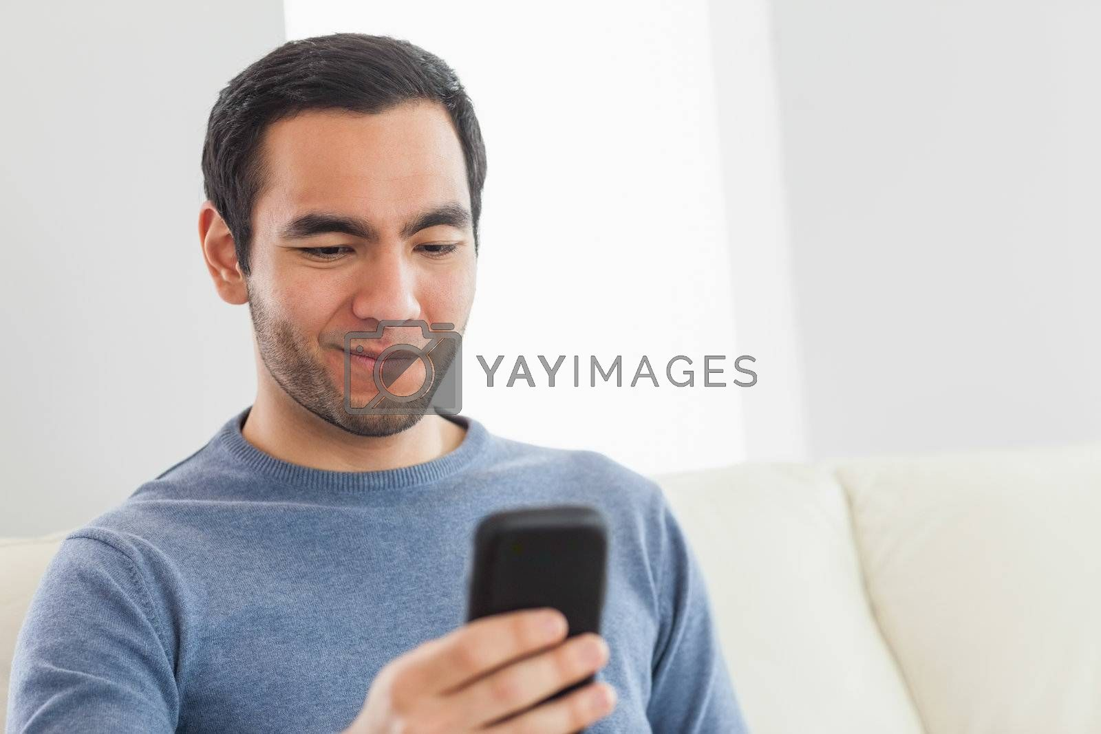 Smiling casual man text messaging by Wavebreakmedia
