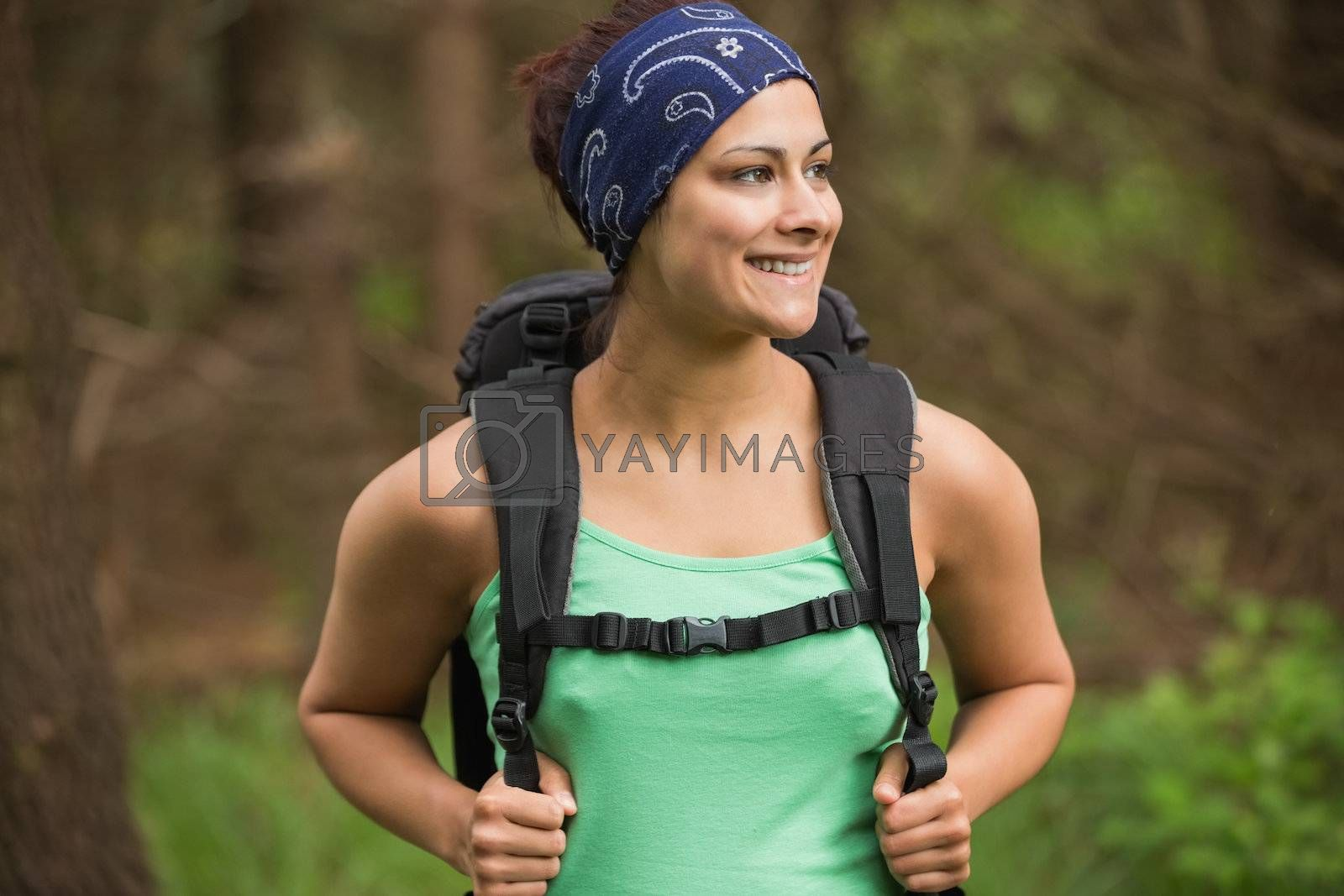 Happy woman standing in a forest by Wavebreakmedia