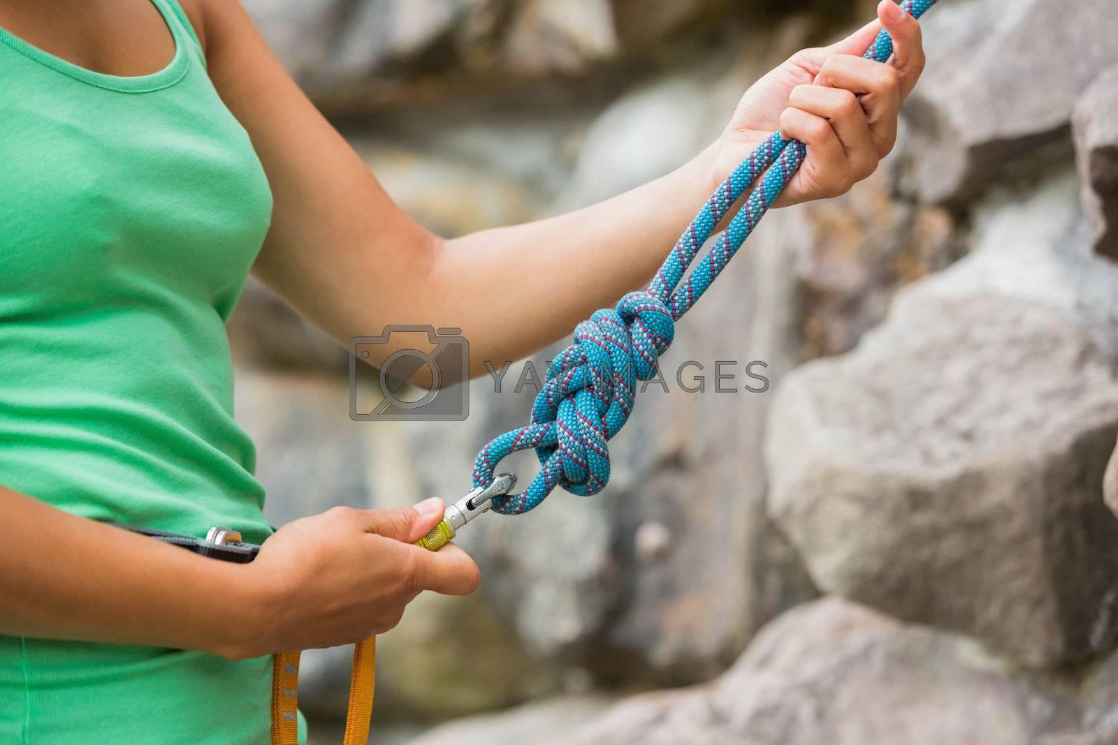Female rock climber adjusting harness by Wavebreakmedia