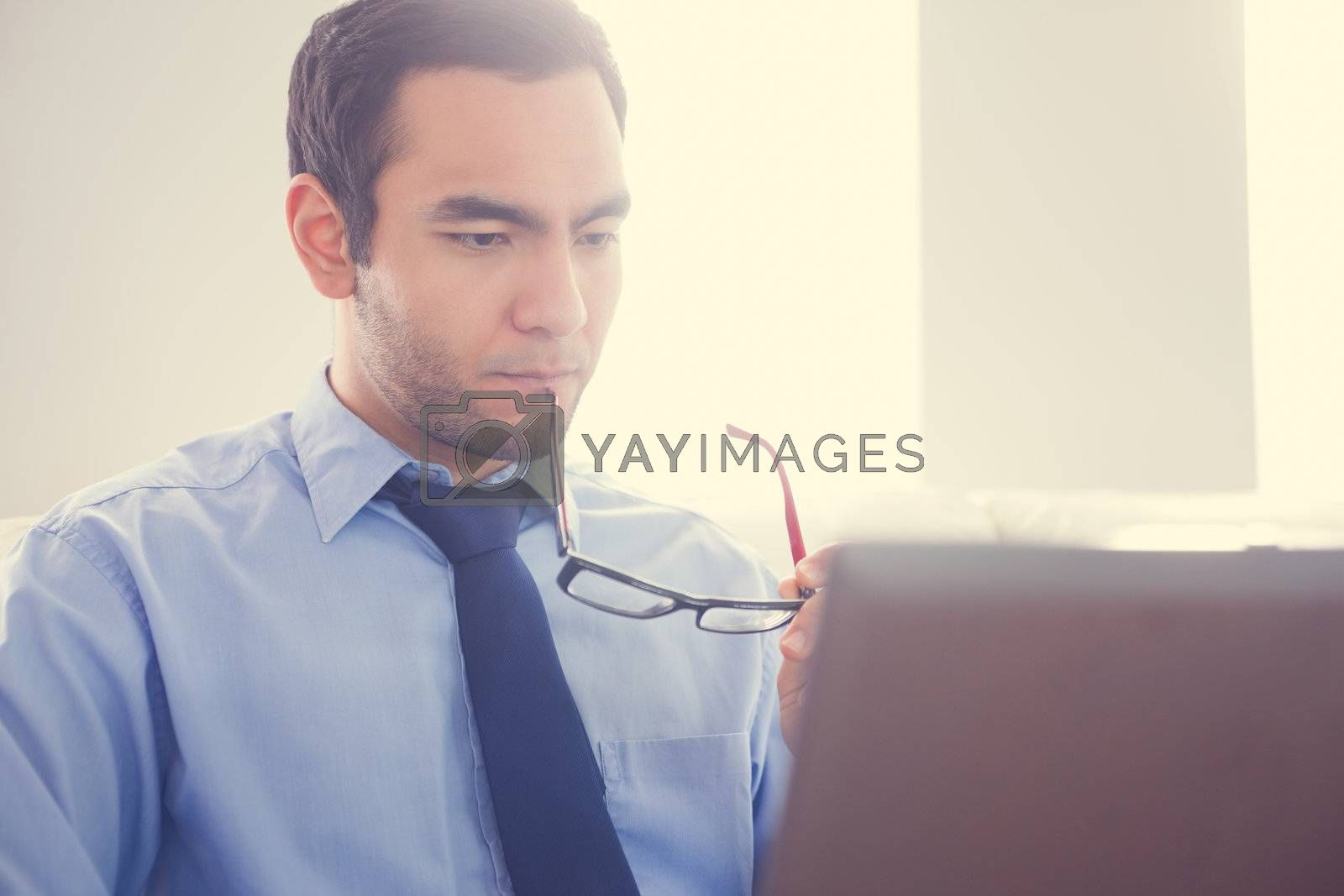 Unsmiling man biting his eyeglasses and using a laptop by Wavebreakmedia