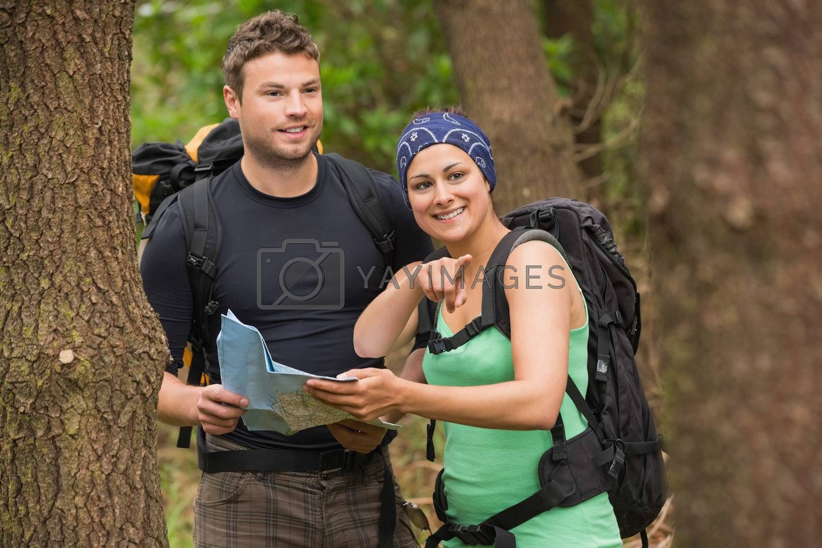 Fit couple reading map in a forest with woman pointing by Wavebreakmedia