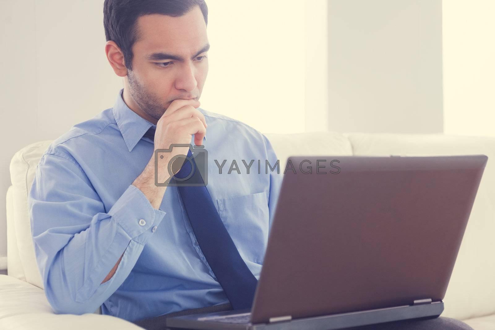 Stressed man using a laptop sitting on a sofa by Wavebreakmedia