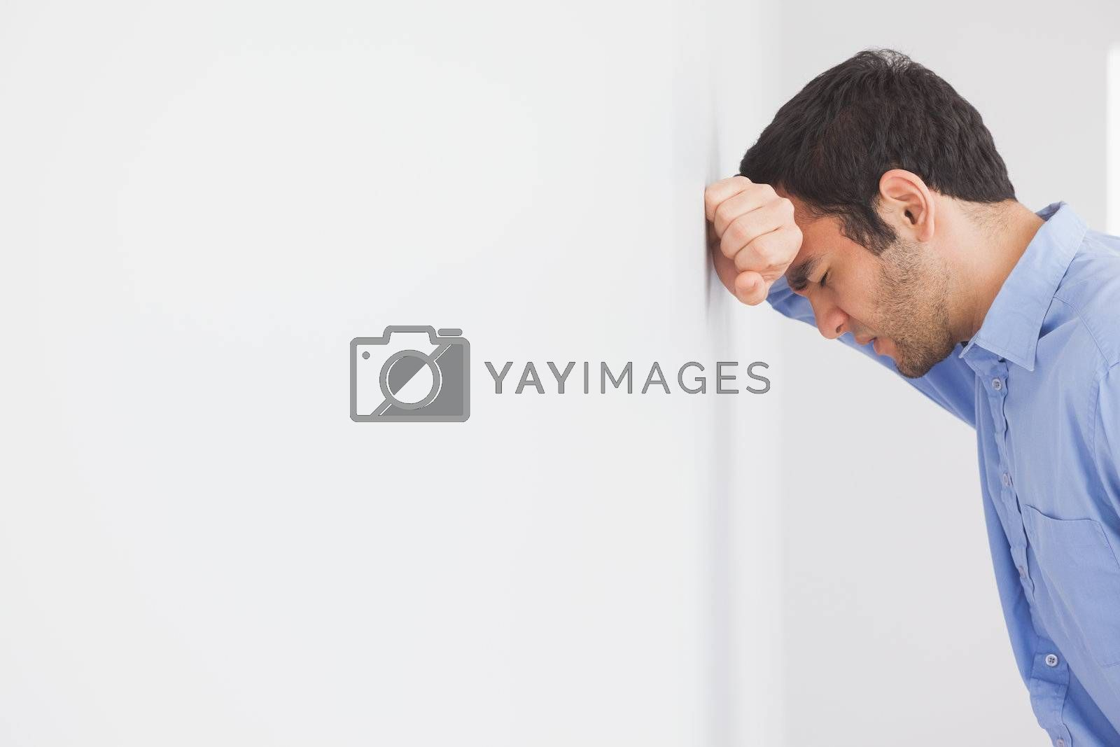 Angry man leaning his head against a wall by Wavebreakmedia