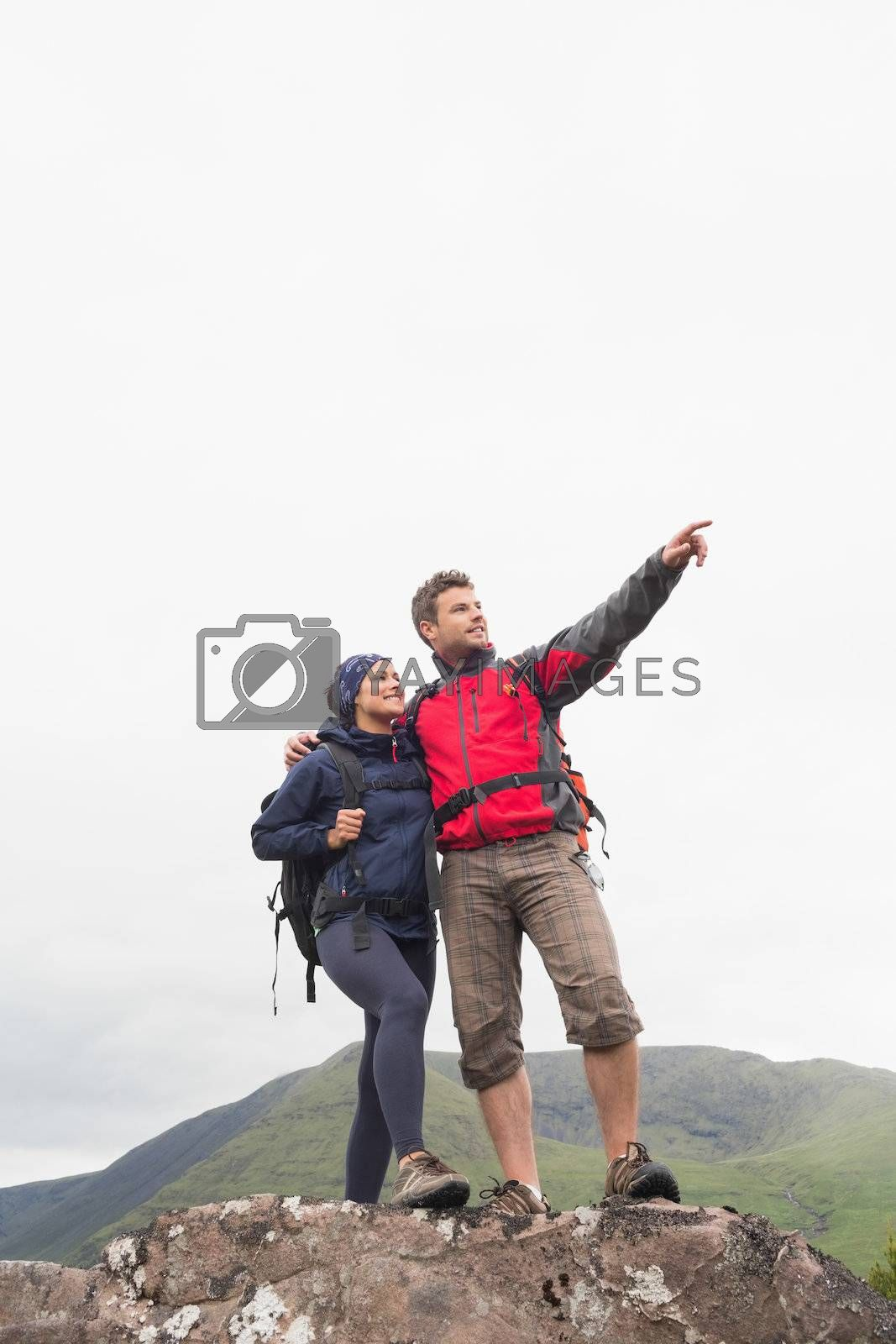 Couple standing on rock looking up at the mountains by Wavebreakmedia