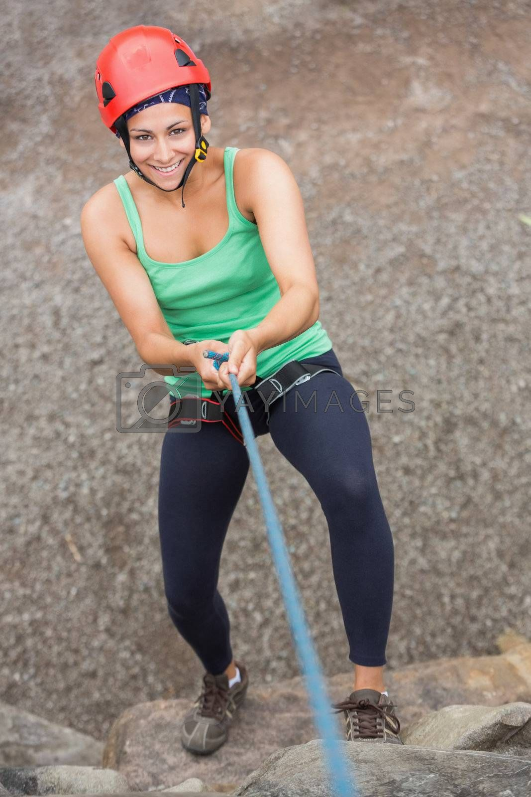 Smiling girl abseiling down rock face  by Wavebreakmedia