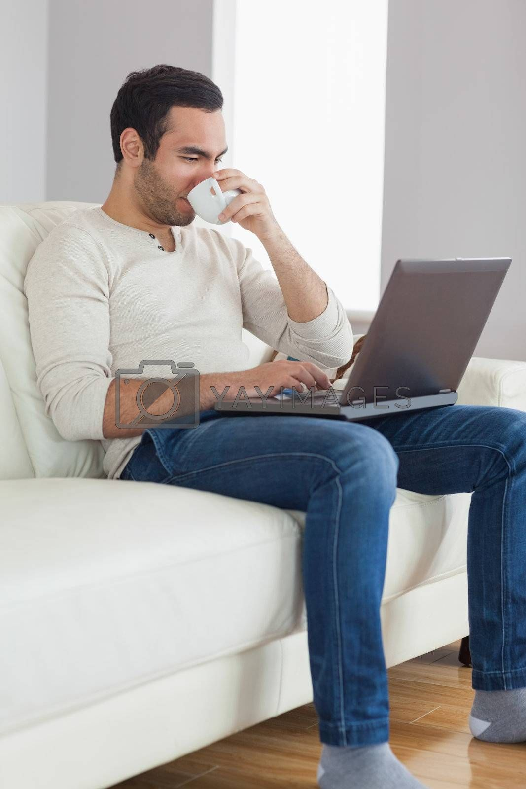 Relaxed attractive man drinking coffee while working on his laptop by Wavebreakmedia