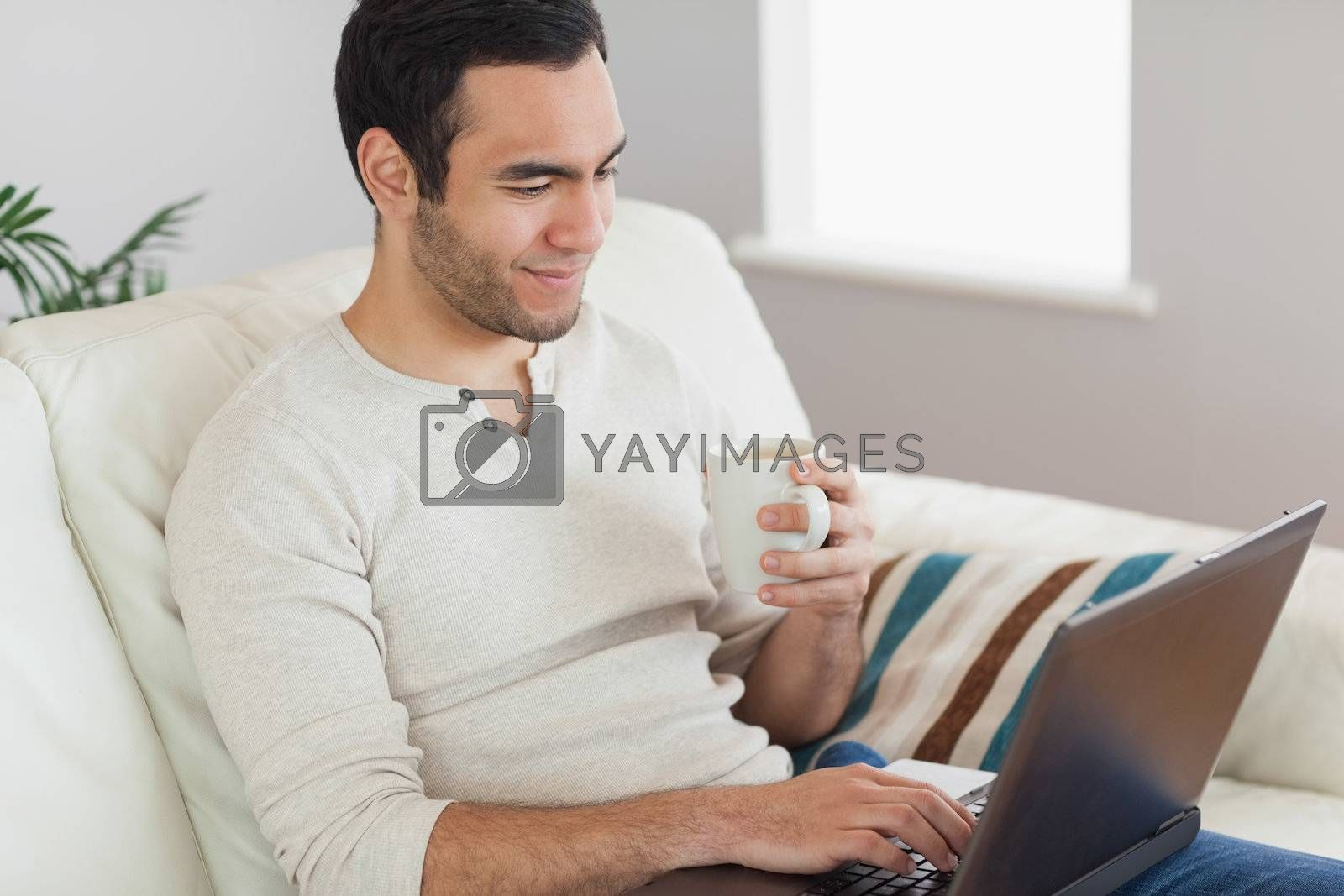 Calm attractive man drinking coffee while working on his laptop by Wavebreakmedia