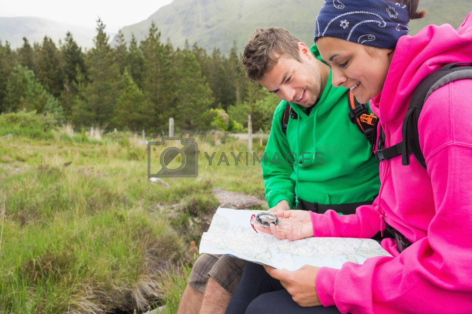 Couple sitting on a rock resting during hike using map and compass by Wavebreakmedia