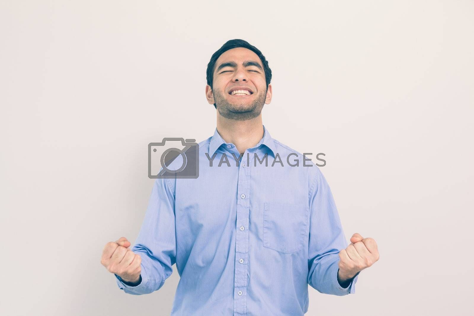 Victorious man standing clenching his fists  by Wavebreakmedia
