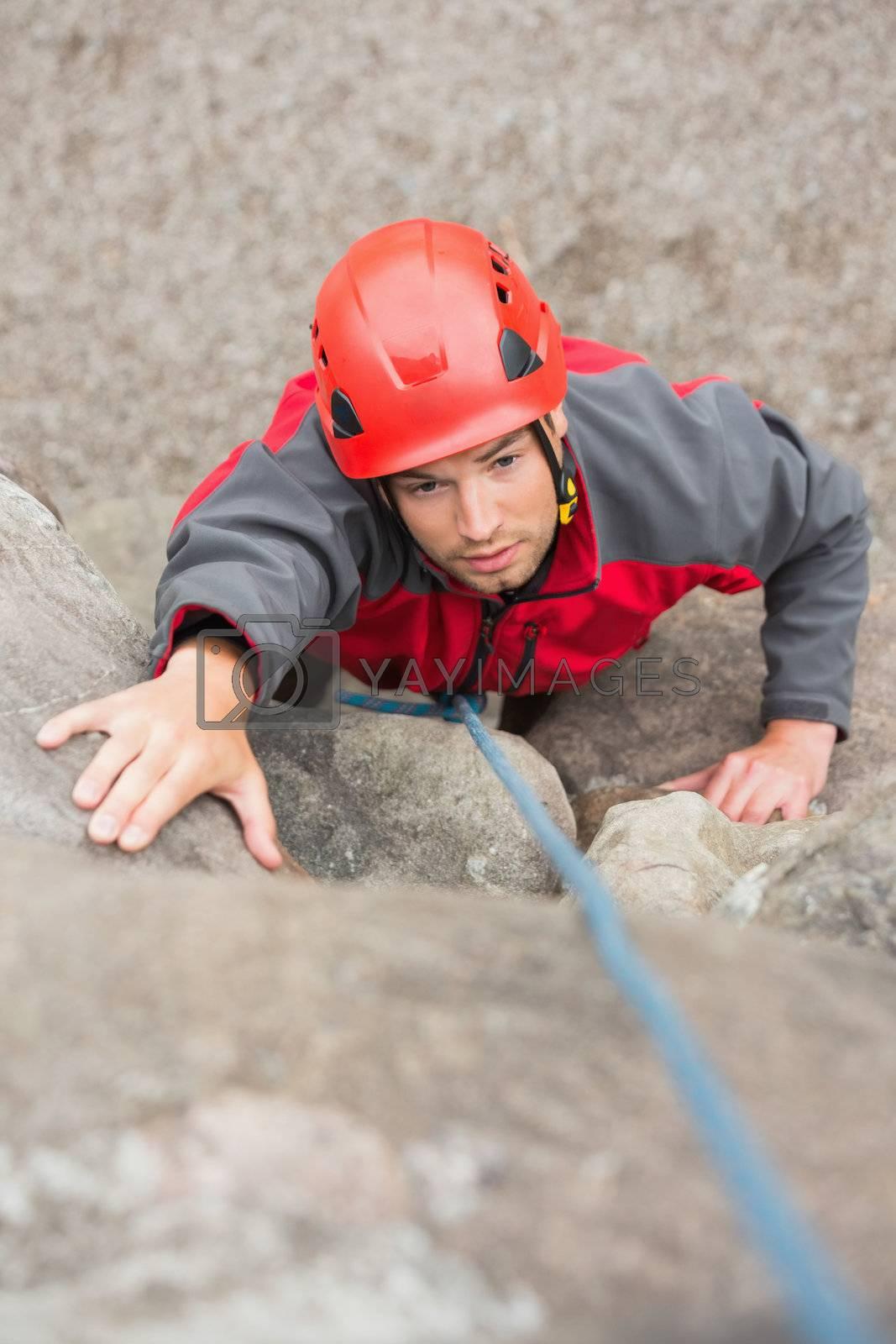 Focused man climbing rock face by Wavebreakmedia