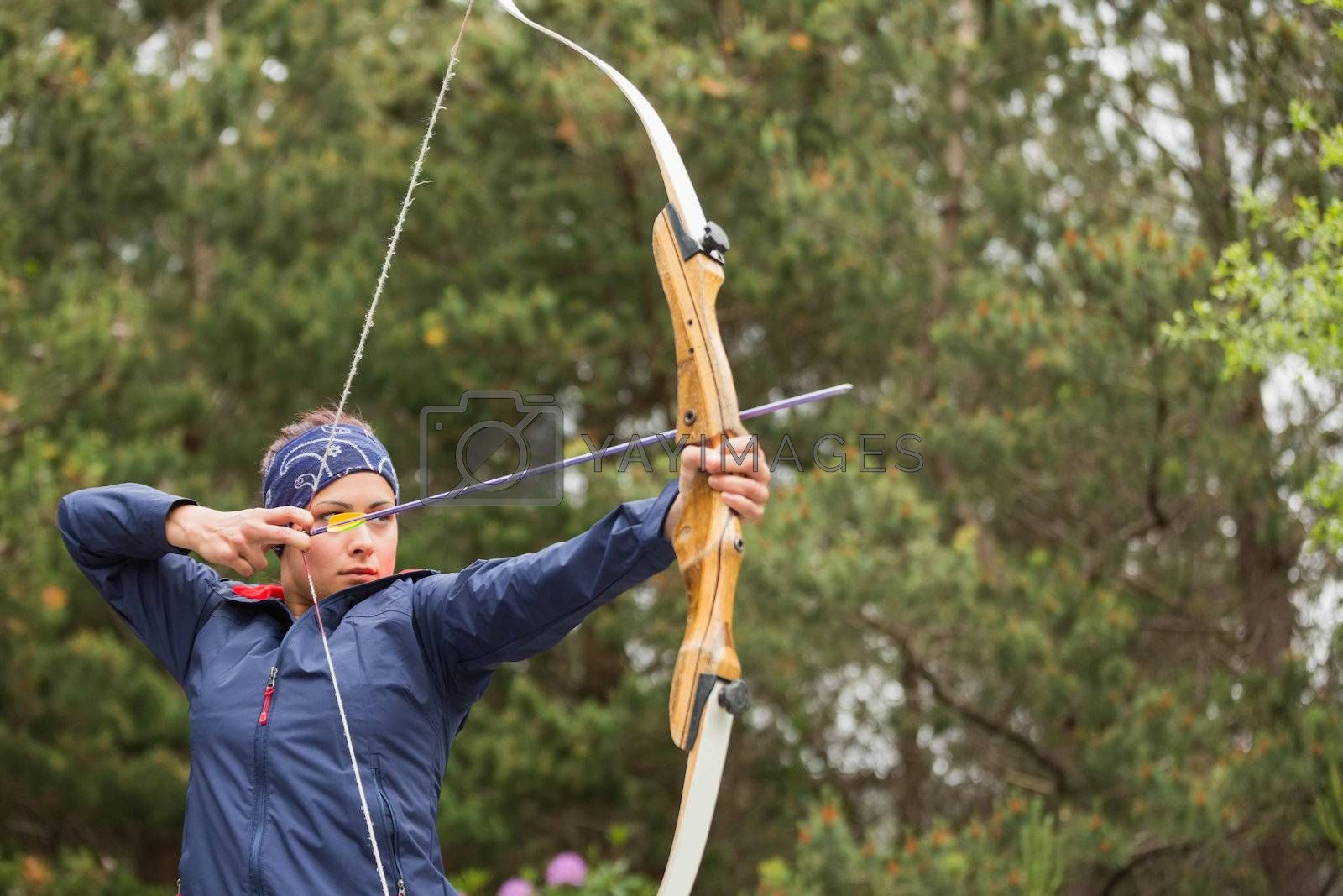 Concentrating brunette practicing archery by Wavebreakmedia