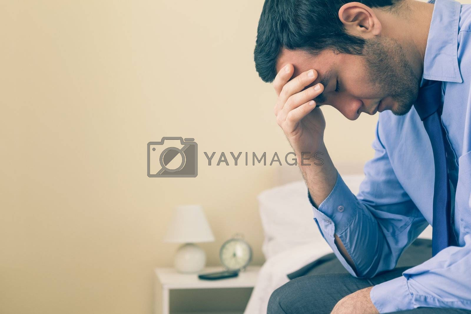 Sad man sitting head in hands on his bed by Wavebreakmedia